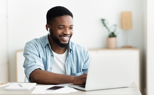 Smiling african american guy in earphones studying foreign language online
